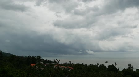 Dramatic gloomy sky with dark thunderstorm clouds over turquoise sea. Hurricane on ocean horizon. Vivid aerial timelapse beautiful view of storm raining seascape. Tropical rain season, typhoon weather Stock mozgókép