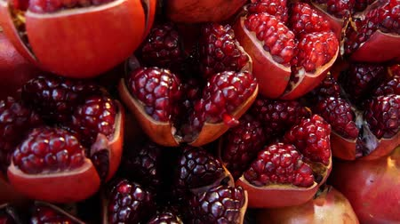 Halves of ripe pomegranates for juice. Heap of halves of yummy ripe pomegranates for fresh juice placed on stall. Vídeos