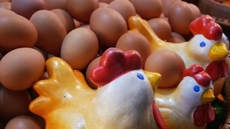 Ceramic chickens near eggs. Closeup lovely ceramic chickens placed in huge basket with bunch of fresh eggs