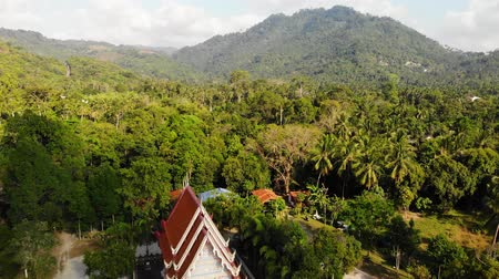 Classic Buddhist temple between forest. From above drone view classic Buddhist monastery between green trees near hill in Thailand. Koh Samui. concept of tourism, meditation and oriental life