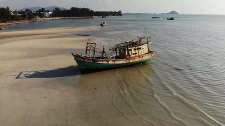 paslanmış : Fishing ship on sand coast near water. Old deserted rusty fishing boat on sand shore near sea in sunny day, koh Samui Aerial drone view Stok Video
