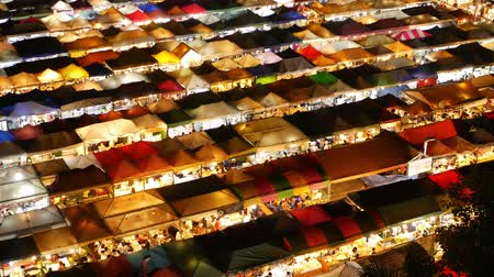 consumo : Illuminated tents of market at night. Top view of colorfull brightly illuminated tents of Ratchada Rot Fai Train Night Market on tourist street of Bangkok. Popular attraction, streetfood and shoping.