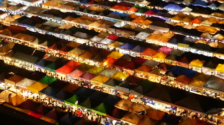 дополнительный : Illuminated tents of market at night. Top view of colorfull brightly illuminated tents of Ratchada Rot Fai Train Night Market on tourist street of Bangkok. Popular attraction, streetfood and shoping.