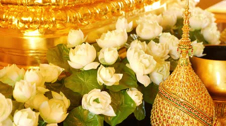 Flowers and golden decorations on altar. Beautiful white lotus flowers and golden royal ornaments placed on traditional altar in Thailand. Symbol of monarchy