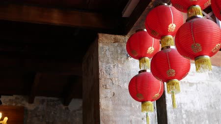 Paper lanterns on shabby building. Red paper lanterns hanging on ceiling of weathered concrete temple building on sunny day in oriental country. traditional decoration.