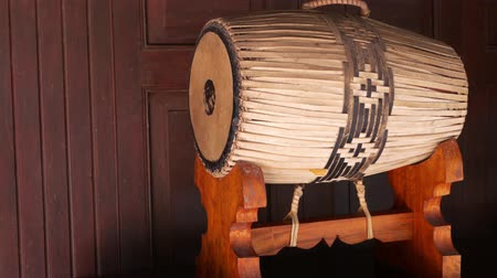 roto : Tradition drum on stand. Traditional Thai drum with ornament placed on wooden stand near lumber wall.
