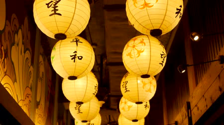 Paper lanterns shining on street. Beautiful paper lanterns shining while hanging in narrow passage on Japanese street. Oriental decor Archivo de Video