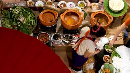 food court : Anonymous woman selling food in Asian food court. Unrecognizable female seller standing near stall and serving traditional Thai food in street food court. Top down view
