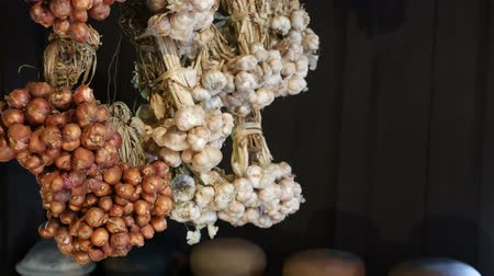 Dried onion and garlic in kitchen. Bunches of small dried onion and garlic hanging against dark wooden wall in kitchen