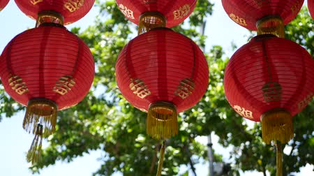 Paper lanterns on shabby building. Red paper lanterns hanging on ceiling of weathered concrete temple building on sunny day between juicy greenery in oriental country. traditional decoration.