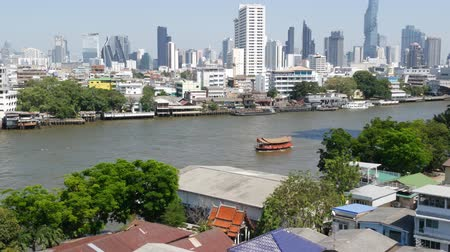 Financial district near calm river. View of skyscrapers located on shore of tranquil Chao Praya river in downtown district of Bangkok. Big city life panorama. Boats on the water in Krungthep Archivo de Video