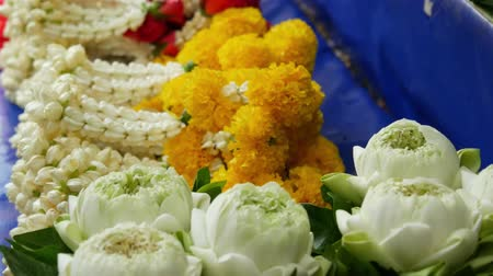 smell : Floral garlands for altar. Assorted flower garlands for ritual sacrifice for sale placed on market stall.