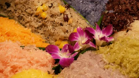 manga : Exotic flowers on mango sticky rice. Closeup beautiful purple orchids placed on portion of colorful traditional Thai sticky rice dessert.