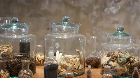 homeopathic : Jars with dried herbs in apothecary shop. Glass jars and bottles with assorted dried medicine herbs placed on shelf in retro oriental pharmacy.