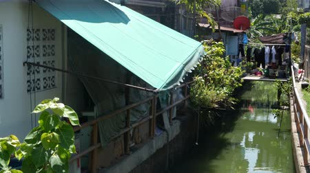 homeopático : Oriental slum near channel. Shabby houses of typical oriental slum located near small canal on street of Bangkok on sunny day. Poor traditional living near water in houses on stilts