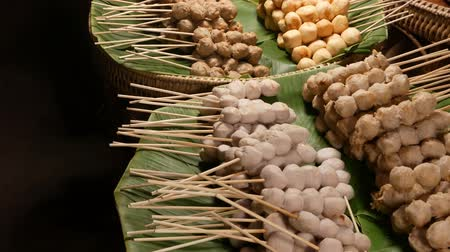 almôndega : Baskets with BBQ meatballs on street. Stacks of delicious traditional barbecue meatballs on sticks placed on green palm leaves in baskets on street of Thailand