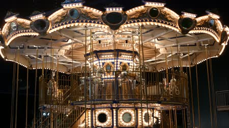 карусель : Illuminated merry go round in park. Brightly illuminated roundabout spinning in wonderful amusement park at night.