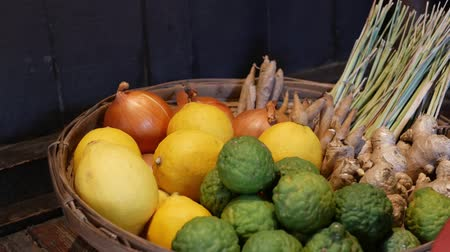 чулан : Basket with fruits and vegetables. Braided basket with various citruses and vegetables placed on floor near wooden wall.