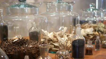 homeopatia : Jars with dried herbs in apothecary shop. Glass jars and bottles with assorted dried medicine herbs placed on shelf in retro oriental pharmacy.