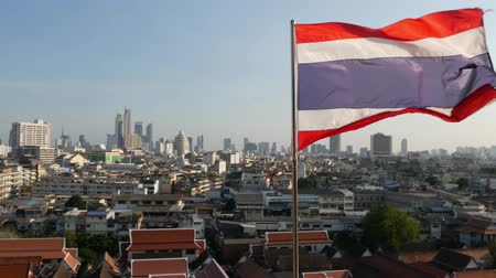 wat : Cityscape of modern oriental town. View of houses roofs on streets of majestic Bangkok from Golden Mount Temple during sunset time. Big flag and symbol of Thailand swaying on the wind.