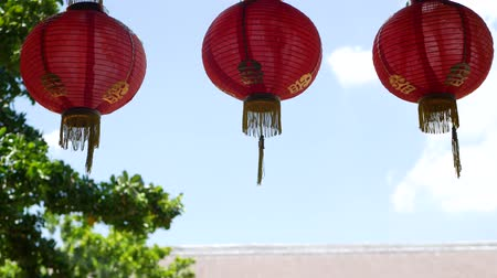 roto : Paper lanterns on shabby building. Red paper lanterns hanging on ceiling of weathered concrete temple building on sunny day between juicy greenery in oriental country. traditional decoration.