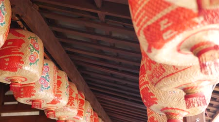 roto : Paper lanterns on shabby building. Red paper lanterns hanging on ceiling of weathered concrete temple building on sunny day in oriental country. traditional decoration.