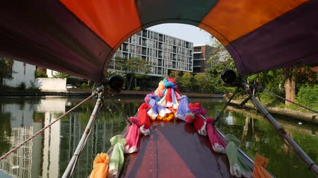 díszített : Tourist trip on Asian canal. View of calm channel and residential houses from decorated traditional Thai boat during tourist trip in Bangkok