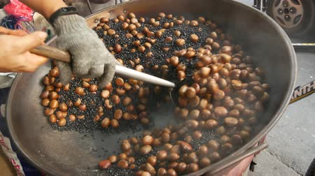 kastanje : Crop hand frying chestnuts. Hand of anonymous man in glove stirring heap of chestnuts on frying pan on street. Stockvideo