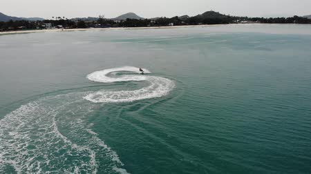 veículo aquático : Anonymous person riding water scooter. Unrecognizable tourist riding modern water scooter on blue water of sea on resort. Koh Samui paradise exotic Chaweng beach drone view