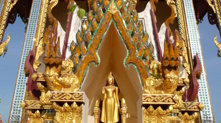 ornamento : Ornamental roof of oriental temple. Golden ornamental roof of traditional Asian temple against cloudless blue sky on sunny day. Wat Plai Laem. Koh Samui. Buddha statue