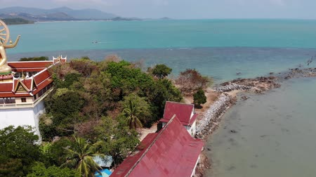 pacific islands : Island with Buddhist temple and many houses. Aerial view of island with Buddhist temple with statue Big Buddha surrounded by traditional houses on stilts in bay of Pacific ocean on Samui, Thailand