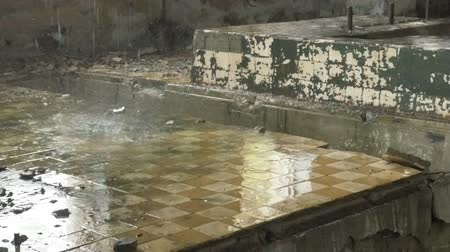 deteriorated : Abandoned factory ruins in raining day , leaking water Stock Footage