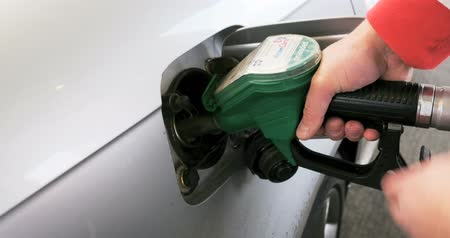benzin : Hand refilling the car with fuel