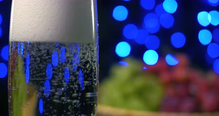 fizzing : Bubbling champagne being poured into two crystal glasses against boke black backgroung Stock Footage