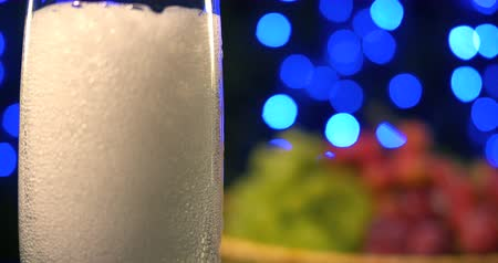 fizzing : Bubbling champagne being poured into two crystal glasses against boke black background Stock Footage