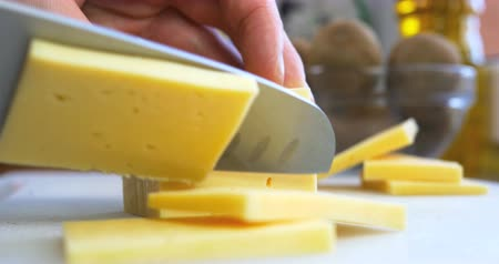 pieces of cheese : Man cutting piece of cheese
