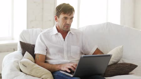 guy home : technology and lifestyle concept - man working with laptop at home