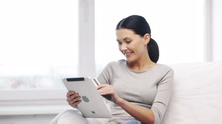 покупатель : home, technology and internet concept - smiling woman sitting on the couch with tablet pc computer and credit card at home Стоковые видеозаписи