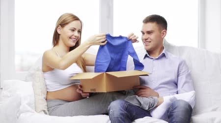 kutu : pregnancy, parenthood, happiness and delivery concept - pregnant mother and happy father looking at baby clothes Stok Video