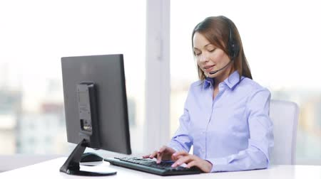 clientes : business and office concept - smiling female helpline operator with headphones and computer at office
