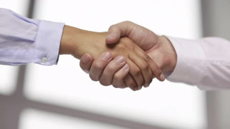 partnerstwo : business and office concept - businessman and businesswoman shaking hands in office