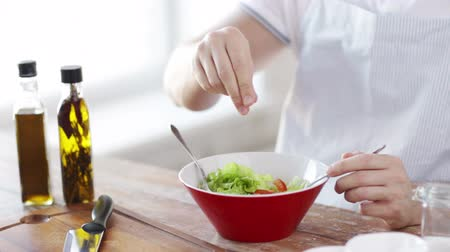 spices : cooking and home concept - close of male hands mixing salad in a bowl