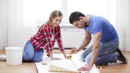 Пол : repair, building and home concept - smiling couple measuring wallpaper