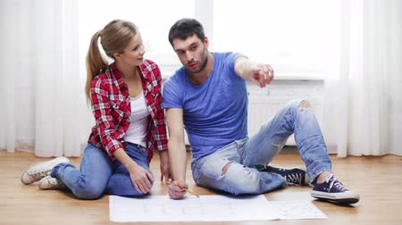 pont : repair, building, renovation and home concept - smiling couple discussin blueprint at home