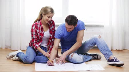 детеныш : repair, building, renovation and home concept - smiling couple discussin blueprint at home