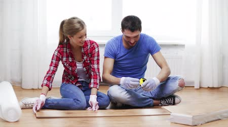 casas : repair, building and home concept - smiling couple measuring wood flooring