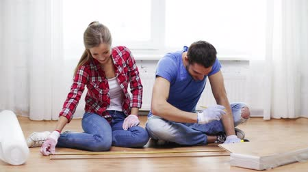 устанавливать : repair, building and home concept - smiling couple measuring wood flooring