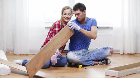 устанавливать : repair, building and home concept - smiling couple taking out wood flooring from package