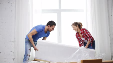 daireler : repair, building and home concept - smiling couple opening big cardboard box with sofa