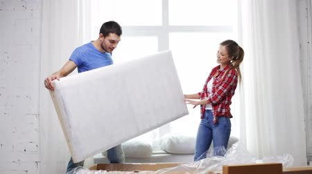 szófa : repair, building and home concept - smiling couple opening big cardboard box with sofa